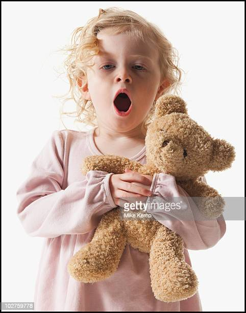 Tired young girl holding teddy bear
