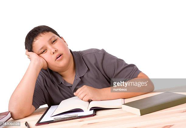 Tired young male student with books in front of him