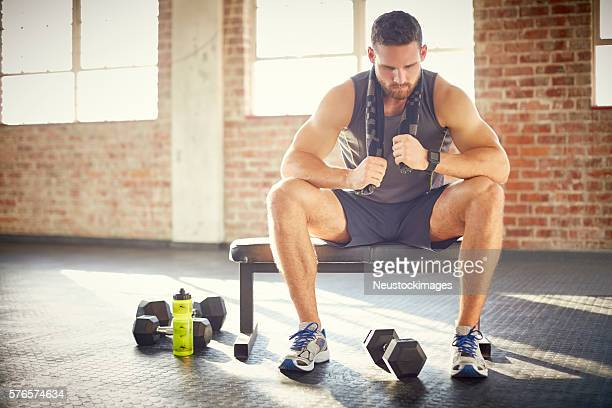 Tired young man sitting on bench in gym