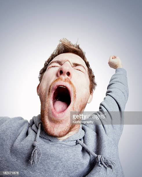 Tired Young Man Stretching and Yawning with Open Mouth