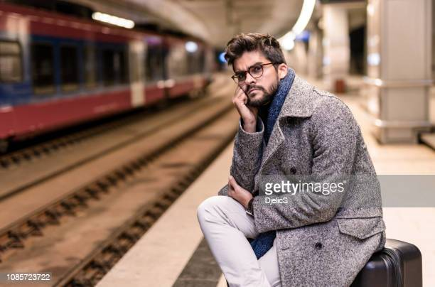 müde junger mann warten auf einen zug in der nacht. - frist stock-fotos und bilder