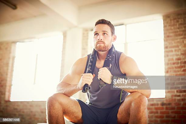 Tired young man with towel around neck in gym