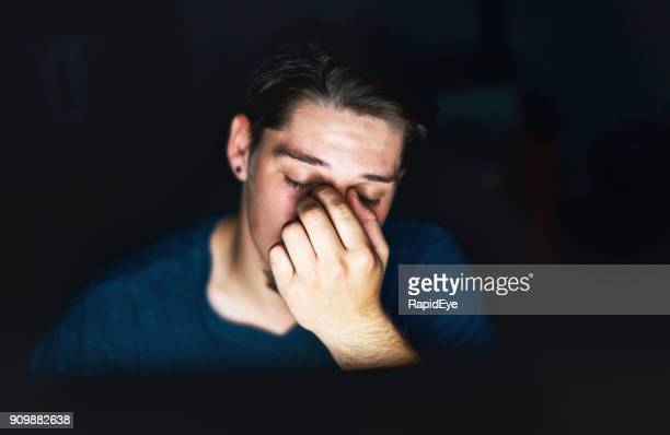 Tired young man working late lit by computer rubs eyes