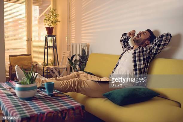 Müde junge Mann Gähnen im Wohnzimmer.