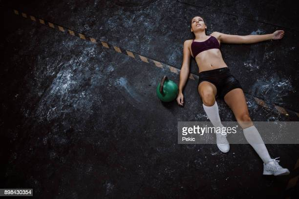 tired young woman lying down in gym - one young woman only stock pictures, royalty-free photos & images