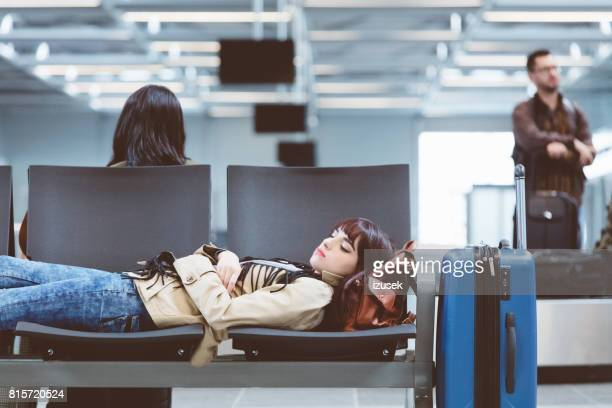 Tired young woman sleeping at airport with luggage