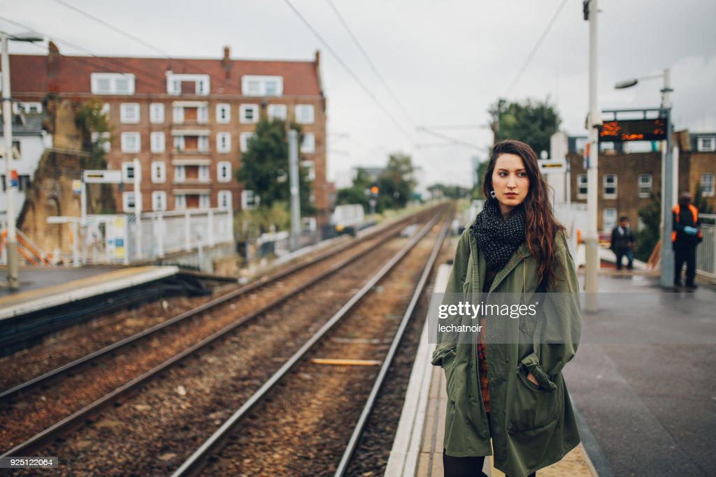 tired young woman waiting for the public transportation in London, UK : Stock Photo