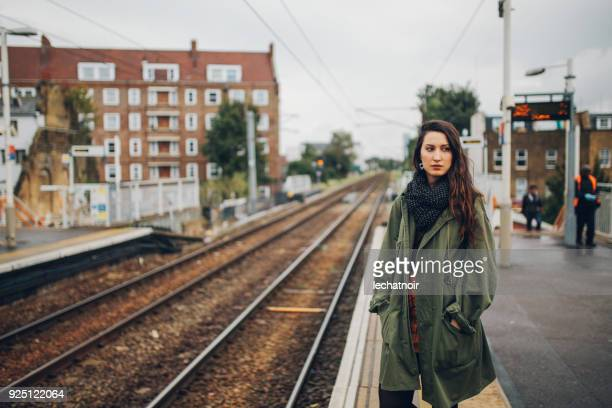 tired young woman waiting for the public transportation in london, uk - parka coat stock photos and pictures