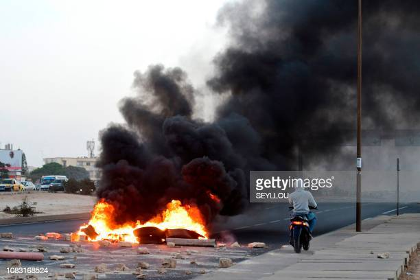 Tires burn on a motorway in the north of Dakar during a revolt of supporters of Khalifa Sall in front of the headquarters of the liberal Bokk Gis Gis...