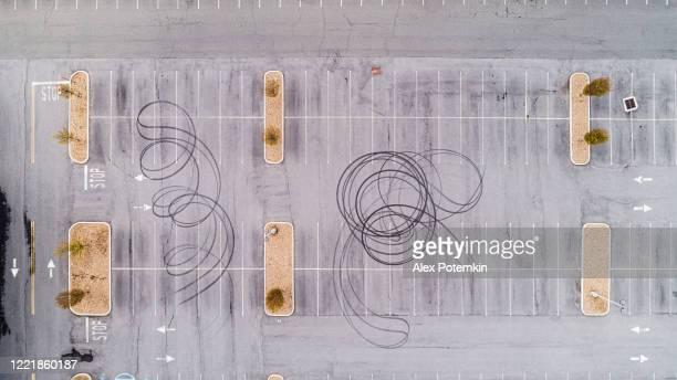 bandensporen op het asfalt achtergelaten door fietsers die de parkeerplaats voor het gesloten zakencentrum gebruikten voor drift en racen. extra groot gestikt panorama. - spoor vorm stockfoto's en -beelden