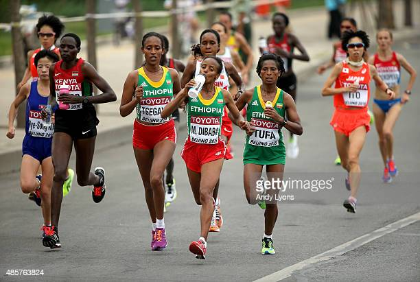 Tirfi Tsegaye of Ethiopia, Mare Dibaba of Ethiopia and Tigist Tufa of Ethiopia drink from water bottles as they lead the field during the Women's...