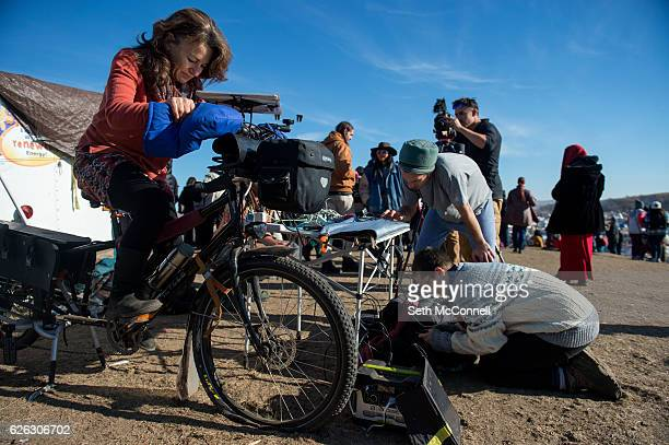 Tirzah Firestone rides a bike to create energy that will be stored in a battery to help charge cellphones at Oceti Sakowin Camp on the Standing Rock...
