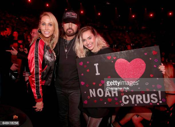 Tish Cyrus and singerssongwriters Billy Ray Cyrus and Miley Cyrus pose with a sign reading 'I heart Noah Cyrus' during the 2017 iHeartRadio Music...