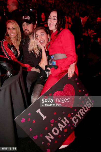 Tish Cyrus and singerssongwriters Billy Ray Cyrus Miley Cyrus and Noah Cyrus pose with a sign reading 'I heart Noah Cyrus' during the 2017...