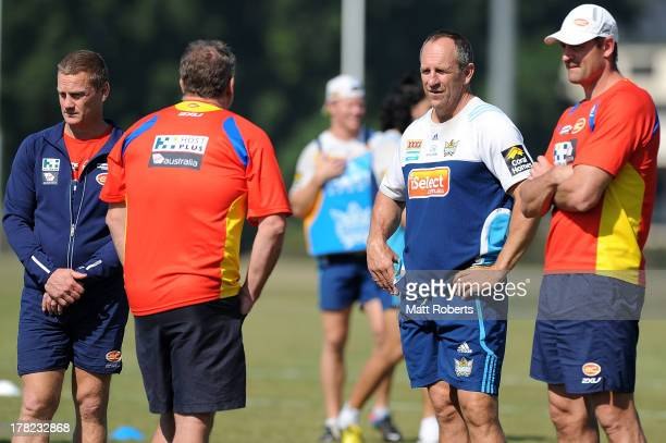Titans coach John Cartwright speaks with Suns coach Guy McKenna during a Gold Coast Titans training session at Metricon Stadium on August 28 2013 on...