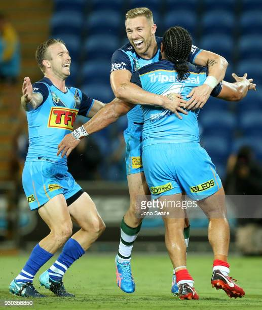 Titans players Kane Elgey and Bryce Cartwright celebrate Konrad Hurrell's try during the round one NRL match between the Gold Coast Titans and the...