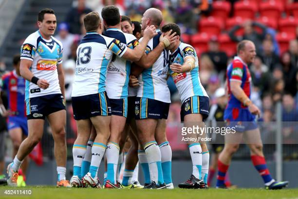 Titans team mates celebrate a try with Knights players looking dejected during the round 19 NRL match between the Newcastle Knights and Gold Coast...