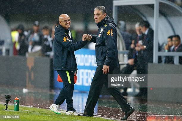 Tite coach of Brazil celebrates with his assistant after Willian scored the second goal of his team during a match between Venezuela and Brazil as...