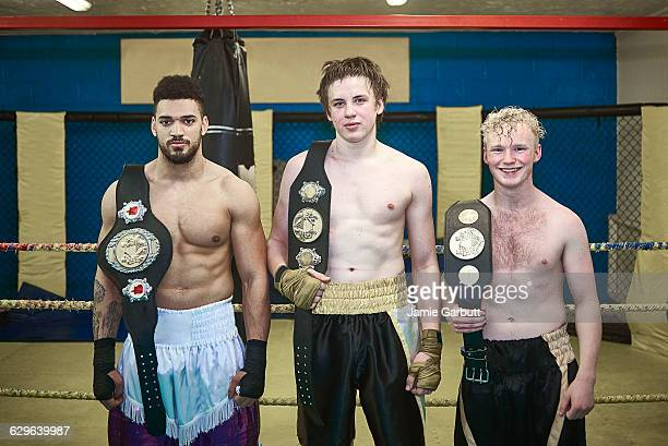 3 title holding boxers stood proudly in a ring - boxing belt stock pictures, royalty-free photos & images