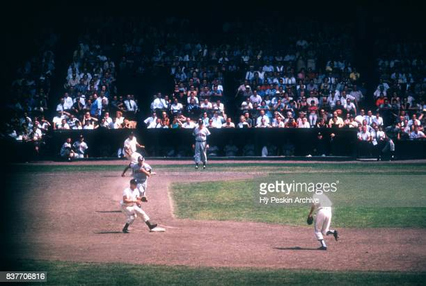 Tito Francona of the Cleveland Indians is called out at second base as Rocky Bridges and Coot Veal of the Detroit Tigers turn the double play during...
