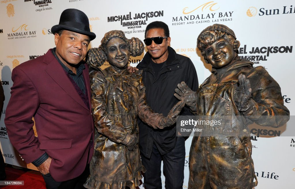 Tito Jackson (L) and Jackie Jackson (3rd L) pose with Cirque du Soleil performers as they arrive at the Las Vegas premiere of Michael Jackson THE IMMORTAL World Tour by Cirque du Soleil at the Mandalay Bay Resort & Casino December 3, 2011 in Las Vegas, Nevada.