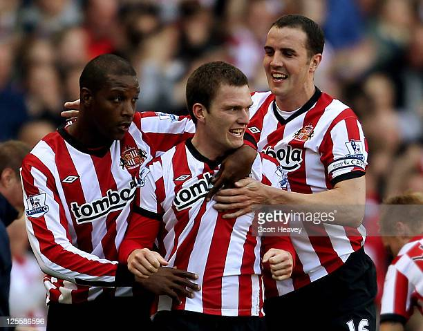 Titus Bramble and John O'Shea celebrate with Craig Gardner after he scored their third goal during the Barclays Premier League match between...