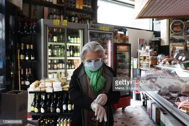 Tiziana from the Cataldi grocery store is preparing to open the shop wearing a protective mask and gloves on March 11, 2020 in Rome, Italy. The...