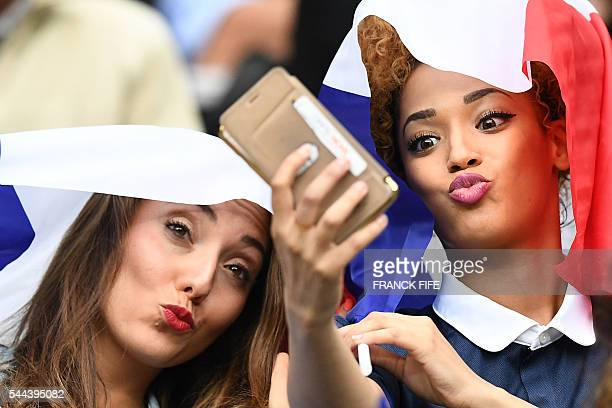 Tiziri Digne the wife of France's defender Lucas Digne and Sephora Coman wife of France's forward Kingsley Coman take a selfie prior to the start of...
