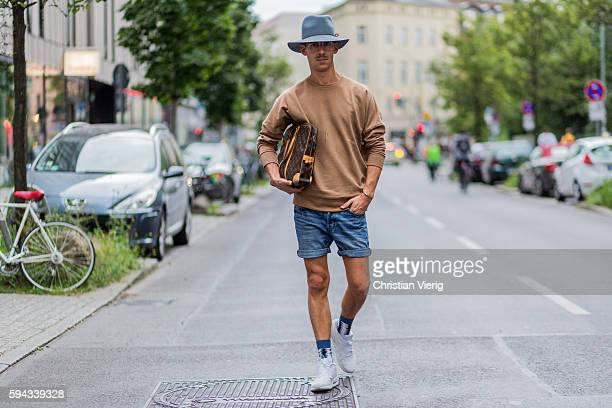 Tjalle Story wearing a beige sweater long shirt Louis Vuitton bag denim shorts a hat glasses socks and white Nike Air Max sneaker on August 22 2016...