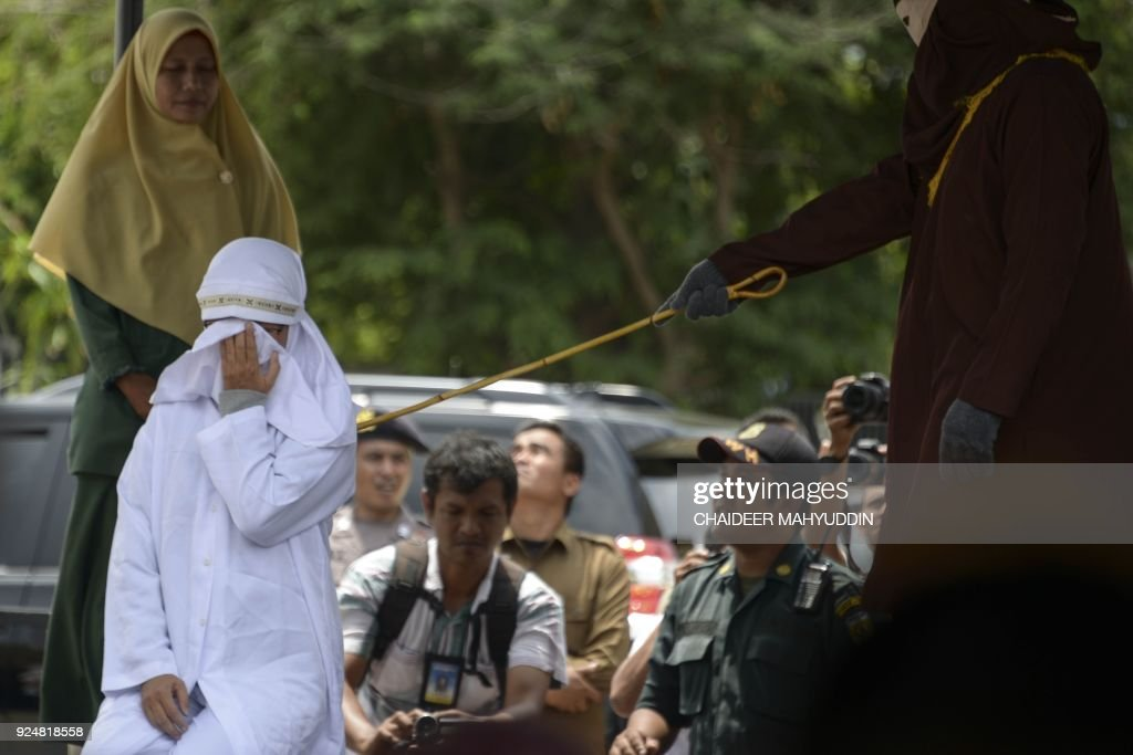 Tjia Nyuk Hwa, 45, an Indonesian Christian is publicly flogged outside a mosque in Banda Aceh on February 27, 2018, for playing a children's entertainment game seen as violating Islamic law. Aceh is the only province in the world's most populous Muslim-majority country that imposes sharia law and people can be flogged for a range of offences -- from gambling, to drinking alcohol to having gay sex or relations outside of marriage. /