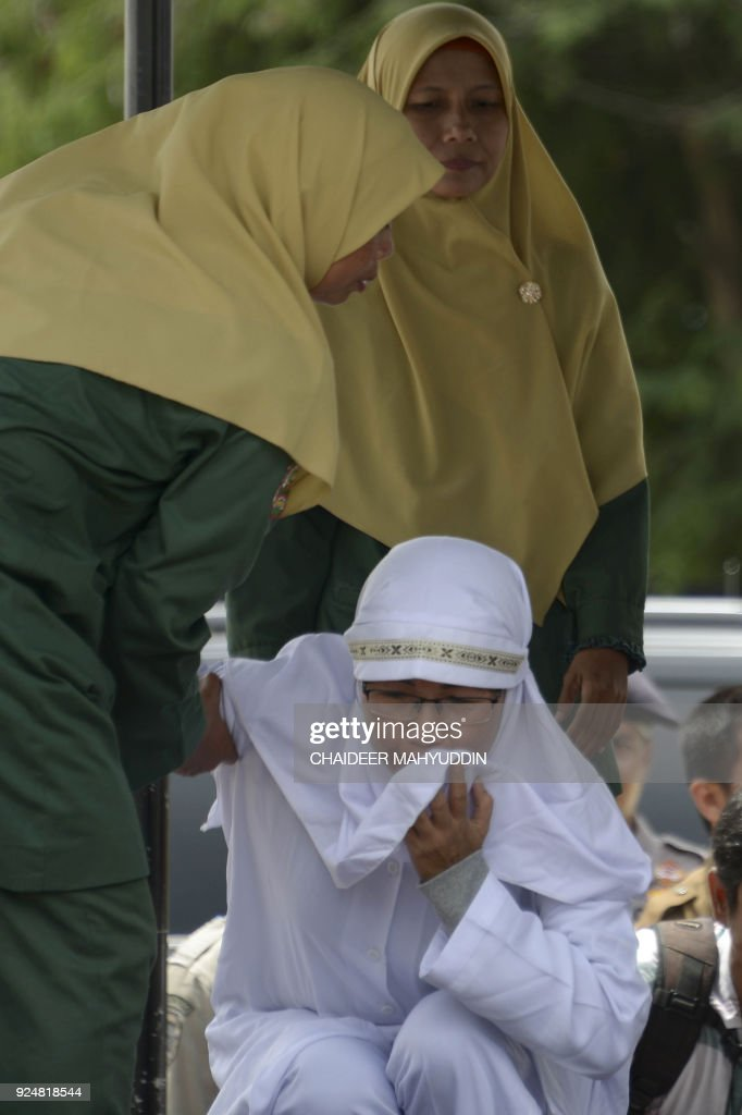 Tjia Nyuk Hwa (lower), 45, an Indonesian Christian prepares to be publicly flogged outside a mosque in Banda Aceh on February 27, 2018, for playing a children's entertainment game seen as violating Islamic law. Aceh is the only province in the world's most populous Muslim-majority country that imposes sharia law and people can be flogged for a range of offences -- from gambling, to drinking alcohol to having gay sex or relations outside of marriage. /
