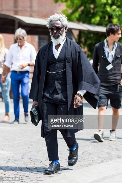 Michael wears a black suit and a black kimono during Pitti Immagine Uomo 92 at Fortezza Da Basso on June 15 2017 in Florence Italy