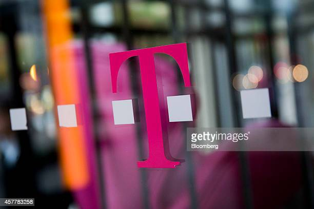 A TMobile US Inc logo hangs in the window at a retail store in Washington DC US on Thursday Oct 23 2014 TMobile US Inc is expected to release third...