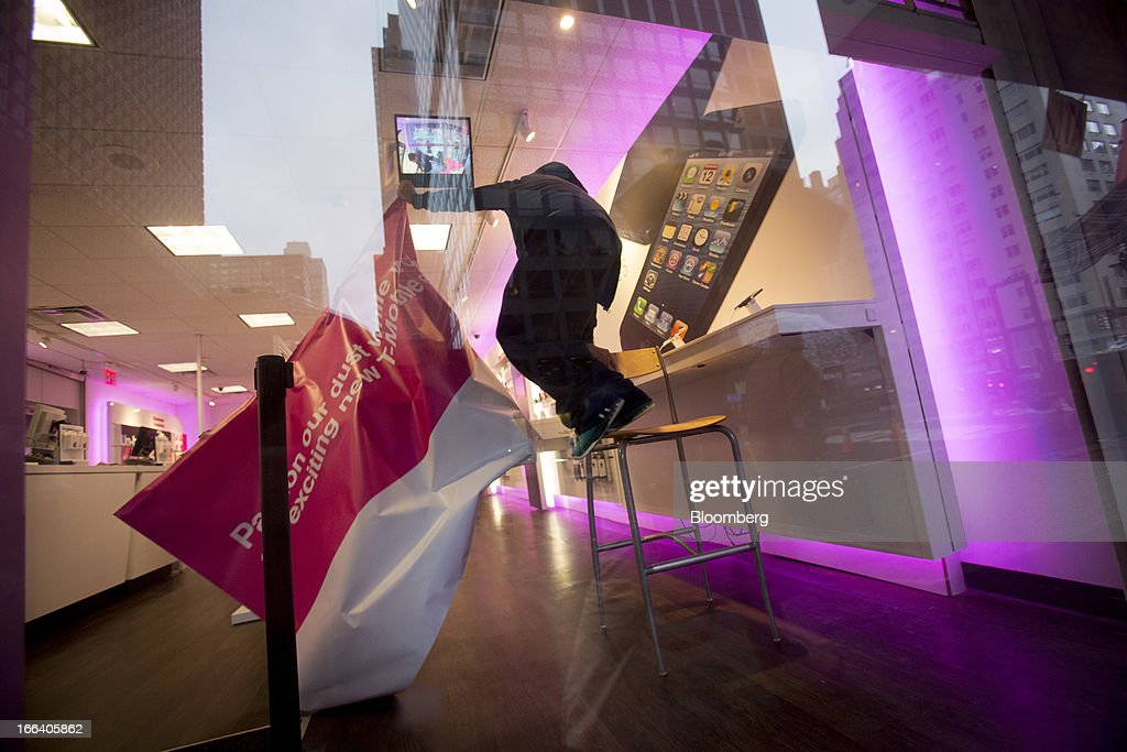 A T-Mobile USA Inc. employee pulls the cover off of an Apple Inc. iphone 5 display at a retail location in New York, U.S., on Friday, April 12, 2013. T-Mobile USA Inc., the fourth-largest U.S. wireless carrier, will begin offering Apple Inc.'s iPhone for the first time today, providing the biggest showcase yet for its new installment-plan approach to selling phones. Photographer: Scott Eells/Bloomberg via Getty Images