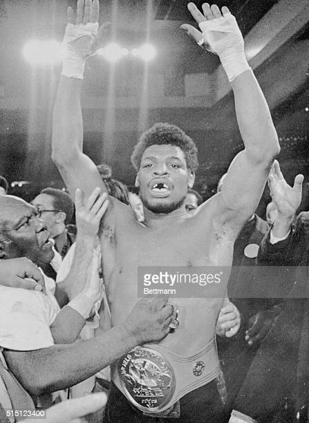 10 to 1 underdog Leon Spinks is surrounded by his entourage in the ring in this photograph as he raises his arms in victory while sporting his...