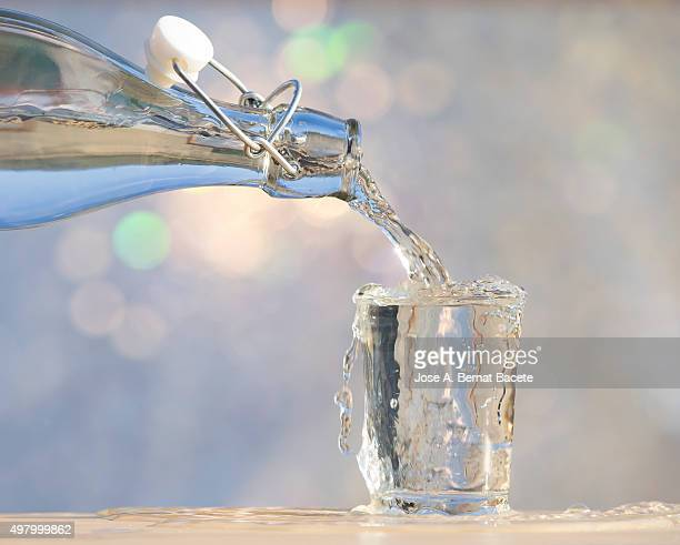 to fill a water glass with a glass bottle - mojado stock pictures, royalty-free photos & images