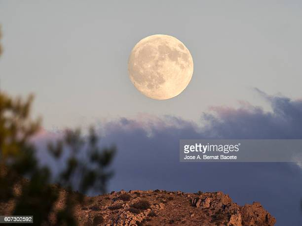 To get dark on the top of a mountain illuminated by the Sun with the full moon