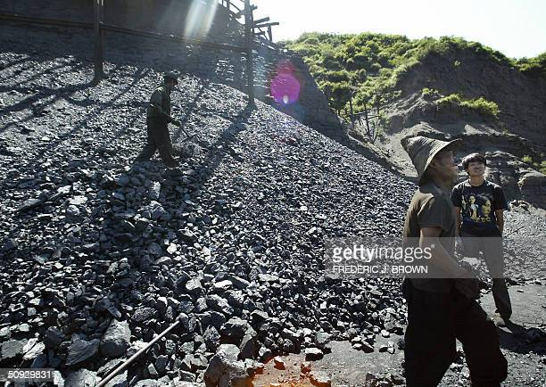 to go w/feature 'CHINACOAL' Blackened by their surroundings workers sort and load coal at a mine in the hills outside of Taiyuan 30 May 2004 in...