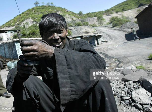to go w/feature 'CHINACOAL' Coalminer Wang Zebang takes a moment to relax after emerging from a long day's work in a coal mine deep in the hills...