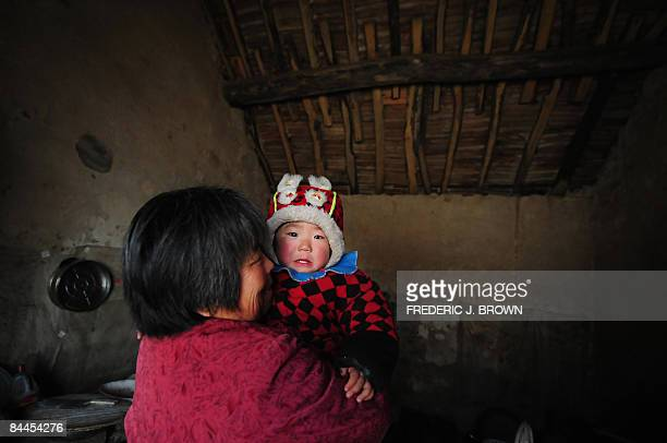 to go w/FinanceeconomyunemploymentLunar by Fran Wang A woman tends to her niece amid the poor surroundings of her home's kitchen in the rural town of...