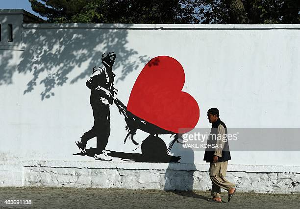 To go with AfghanistanunrestpoliticscorruptionartsFOCUS by Guillaume Decamme In this photograph taken on July 24 an Afghan pedestrian walks past a...
