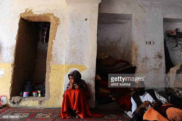 To go with Afghanistanunrestpovertychildren In this October 11 2014 image Afghan child Fatima sits next to her disabled father Ab Zahir at their...