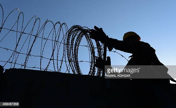 To go with Afghanistan-unrest-US-Bagram,FEATURE by Emmanuel PARISSE In this photograph taken on November 1 a US soldier removes barbed wire from a...