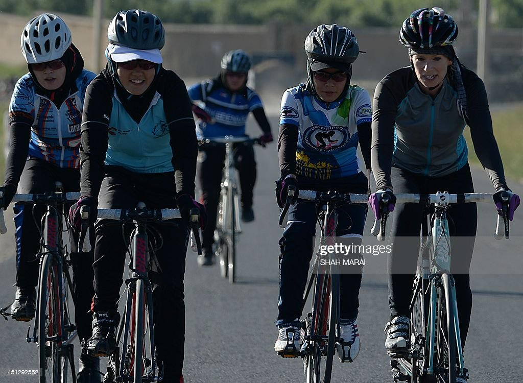 To go with Afghanistan-unrest-women-sport-lifestyle,FEATURE by Anuj CHOPRA This photograph taken on June 9, 2014 shows members of the Afghan national women's cycling team riding their road bikes in Paghman district of Kabul province. Trundling down dun-coloured mountain slopes, they disregard hard stares and vulgarities from passing men, revelling in an activity that seemed unthinkable for previous generations of Afghan women - riding a bicycle. The sight of a woman on a bicycle may not be unusual in most parts of the world, but it is a striking anomaly in Afghanistan where strict Islamic mores deem the sport unbecoming for women. The countrys 10-member national women's cycling team is challenging those gender stereotypes, often at great personal risk, training their eyes not just on the 2020 Olympics but a goal even more ambitious -- to get more Afghan women on bikes. AFP PHOTO/SHAH Marai