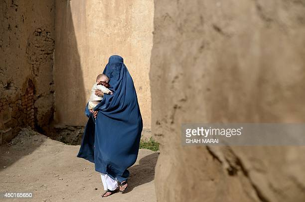 To go with AFP Story 'AfghanistanunrestUSTalibanrights'FOCUS by Anuj CHOPRA In this photograph taken on June 5 a burqaclad Afghan villager carries a...