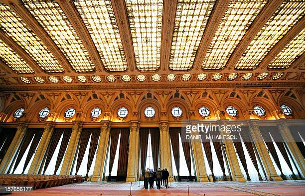 To go with AFP story by Anca Teodorescu Foreign tourists are dwarfed by 'Alexandru Ioan Cuza' hall at the Parliament Palace known as 'The House of...