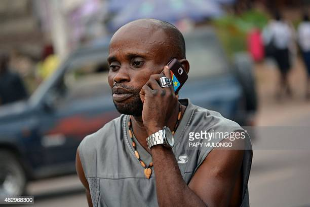 To GO WITH AFP STORY by Habibou BANGRE A local resident uses a mobile phone in Kinshasa on February 4 2015 Small contractors have seen there profits...