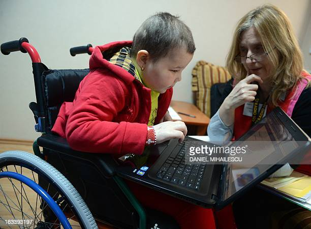 To go with AFP story by Mihaela Rodina AnaMaria Busuioc 10 a cancer suffering Romanian girl learns with a computer helped by psychopedagogue teacher...