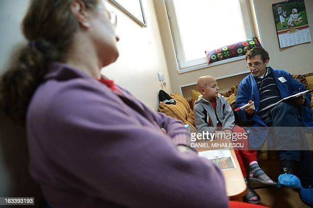 To go with AFP story by Mihaela Rodina Raul Sargu a cancer suffering Romanian boy attends an individual school class watched by his mother at Pavel...