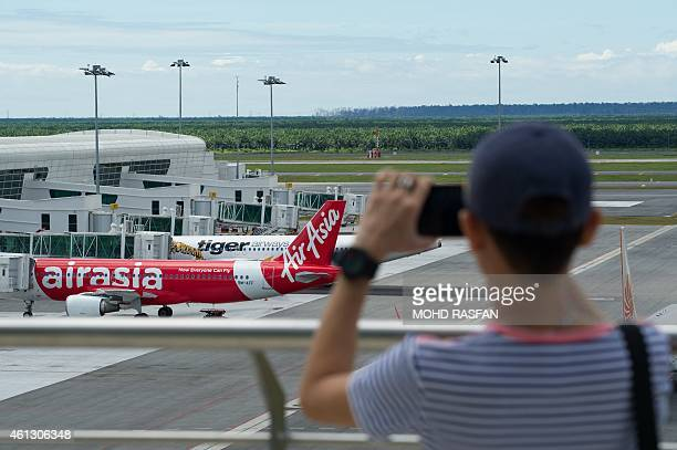 To go with AFP story IndonesiaMalaysiaSingaporeaviationAirAsiacompanyFOCUS by Satish Cheney This photo taken on January 10 2015 shows a man taking...